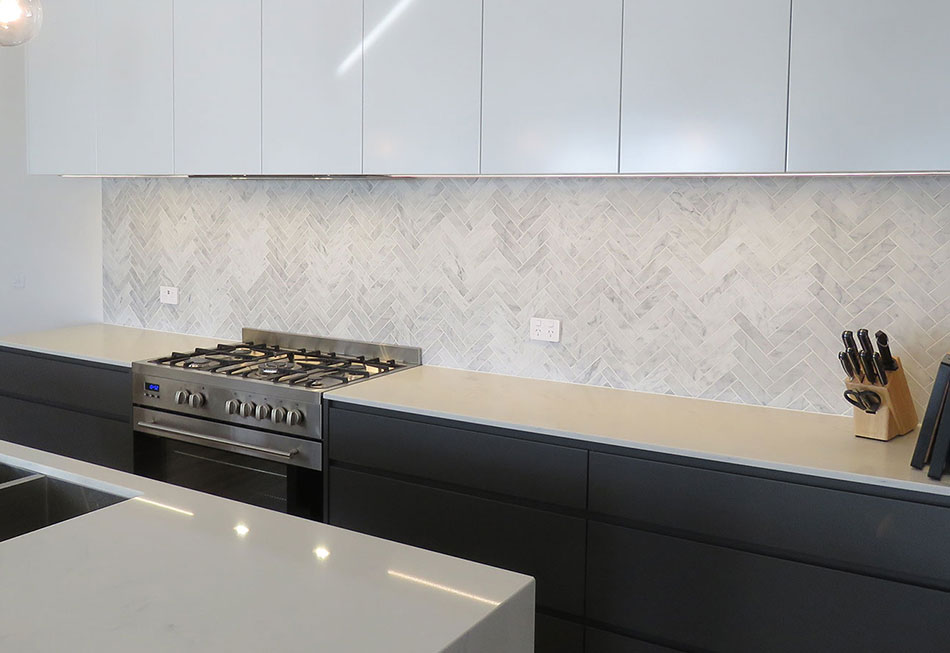 The black cabinetry and neutral tiled splashback creates a modern kitchen